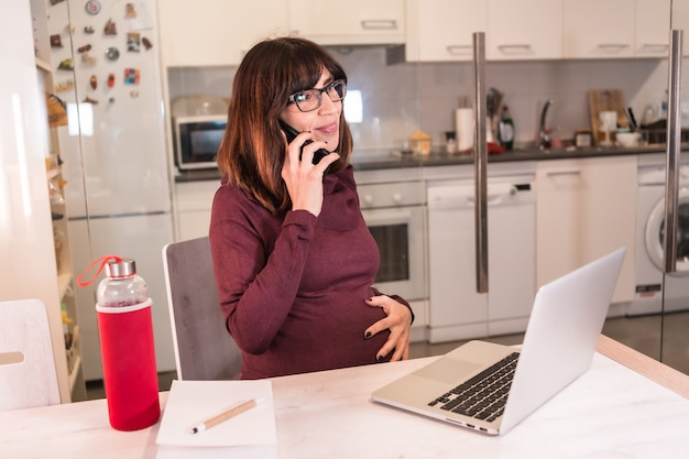 Young pregnant woman teleworking with the computer from home due to the difficulties of working, with a positive attitude on the work call