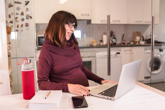 Молодая беременная женщина удаленно работает с компьютером из дома из-за трудностей работы, делая видеозвонок