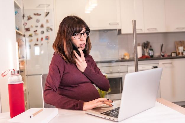 일의 어려움으로 인해 집에서 컴퓨터로 재택 근무하는 젊은 임산부, 직장 전화 걸기