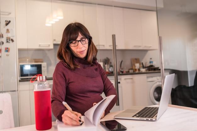 작업의 어려움으로 인해 집에서 컴퓨터로 재택 근무하는 젊은 임산부, 화상 회의에서 메모 작성