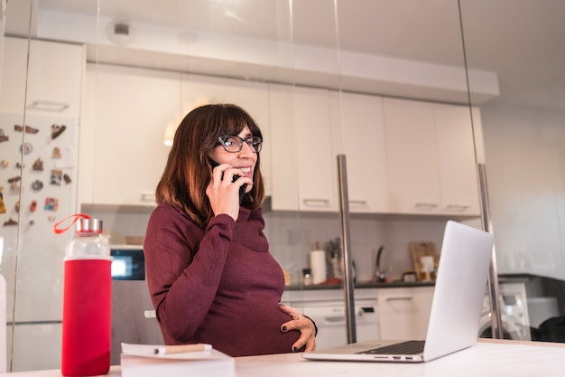 직장 전화에 긍정적 인 태도로 일의 어려움으로 인해 집에서 컴퓨터로 재택 근무하는 젊은 임산부