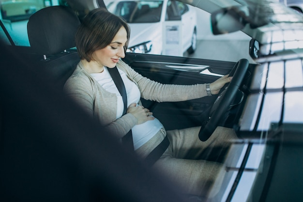 Young pregnant woman testing a car in car showroom