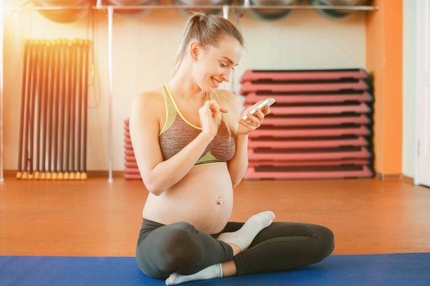 Young pregnant woman using smartphone at the gym