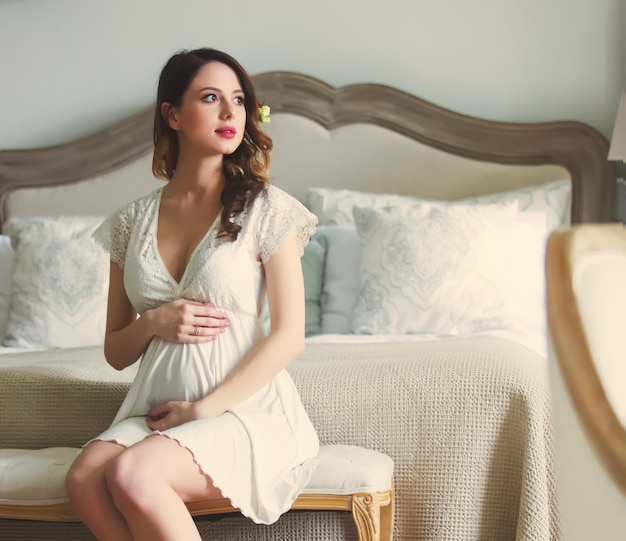 Young pregnant woman in white dress sitting