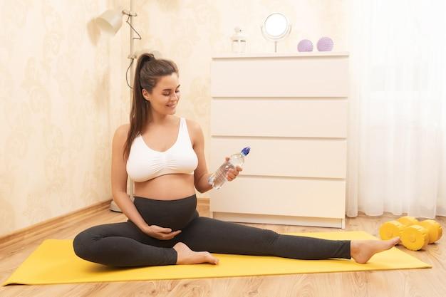 Молодая беременная женщина с бутылкой пресной воды во время фитнес-тренировки дома