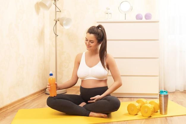 Молодая беременная женщина с бутылкой изотонического напитка во время фитнес-тренировки дома