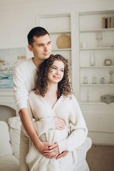 Молодая беременная женщина с мужем обнимаются дома