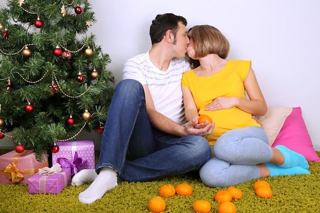 집에서 크리스마스 트리 근처 바닥에 앉아 그녀의 남편과 함께 젊은 임신한 여자