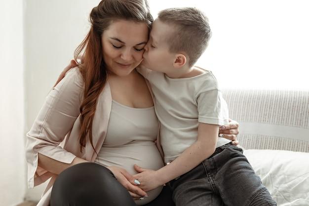 Молодая беременная женщина с маленьким сыном дома на диване, сидя в объятиях.