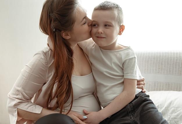 若い妊娠中の女性と幼い息子が自宅のソファに座って抱擁をしています。