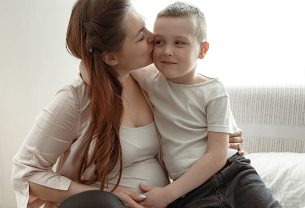 Young pregnant woman with her little son at home on the couch sitting in an embrace.