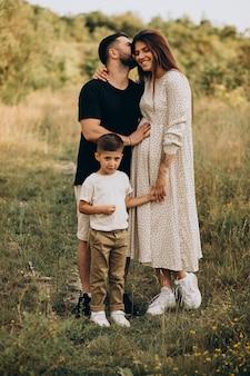 Молодая беременная женщина с мужем и сыном в лесу