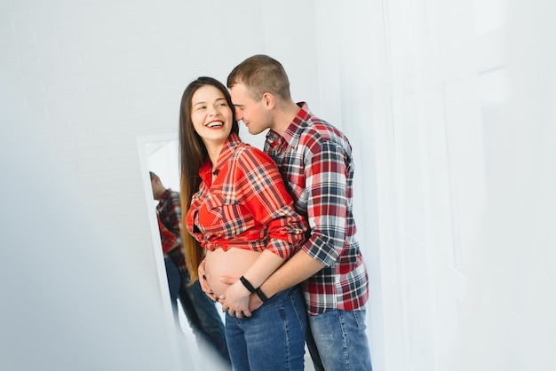 Young pregnant woman with husband posing