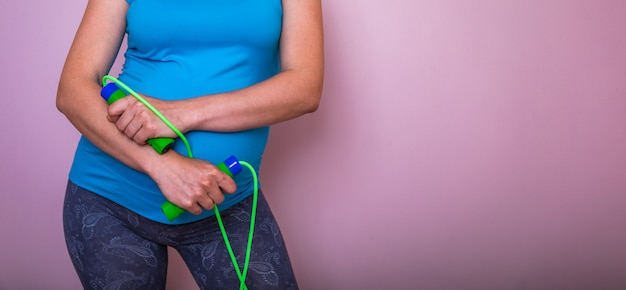 Young pregnant woman with skipping rope or jump rope over pink background