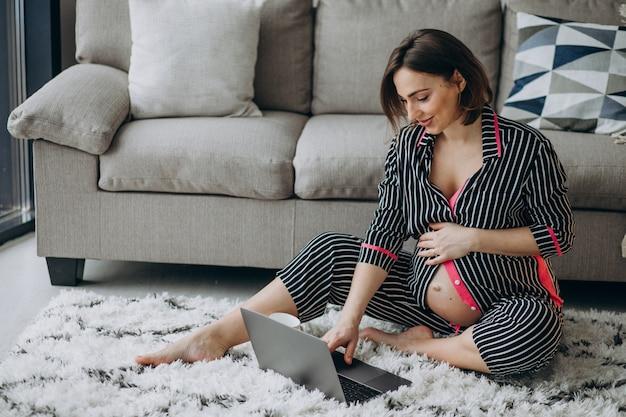 Молодая беременная женщина работает на компьютере у себя дома