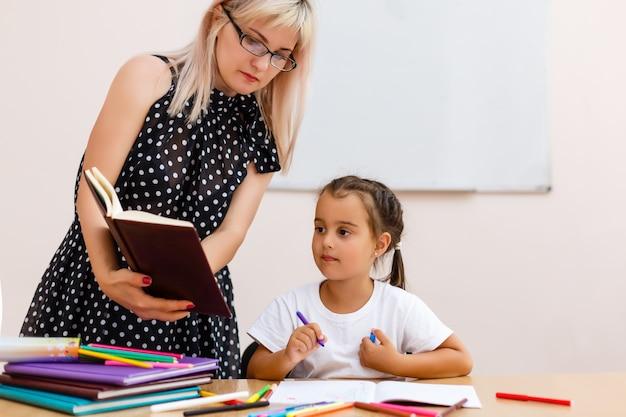 Young preschool teacher teaching little girls in classroom