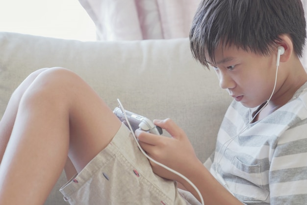 ゲームコンソール、社会的距離、分離、中毒者影響概念を遊んでいる若いプレティーンアジア少年