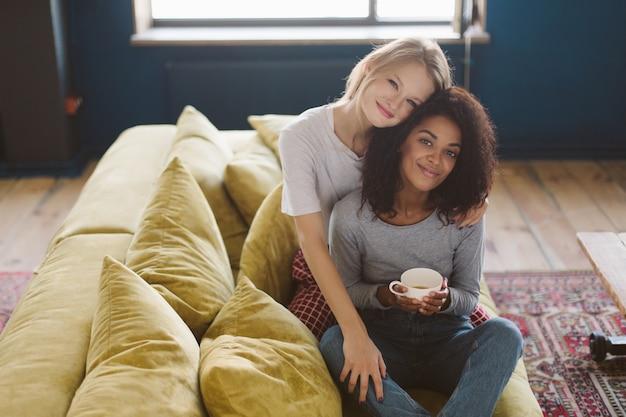 Молодая симпатичная афро-американская девушка с темными вьющимися волосами и улыбающаяся девушка со светлыми волосами счастливо проводит время вместе дома