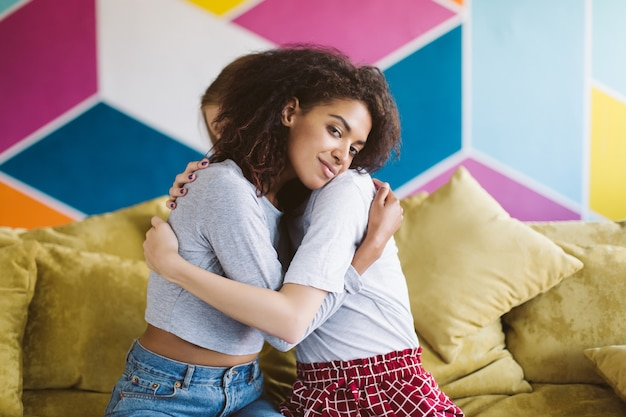 Young pretty african american woman with dark curly hair hugging girlfriend while dreamily  with colorful wall