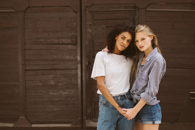 Young pretty african american woman with dark curly hair in t-shirt and jeans and attractive woman with blond hair in shirt and denim shorts dreamily  while spending time together