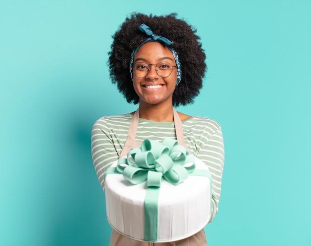 誕生日ケーキを持つ若いかなりアフロパン屋の女性