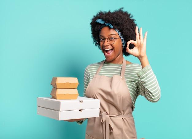 Молодая симпатичная афро доставляет женщину с коробками для пиццы и гамбургеров на вынос