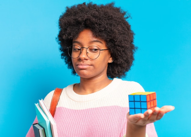 Young pretty afro student woman trying to solve a intelligence problem