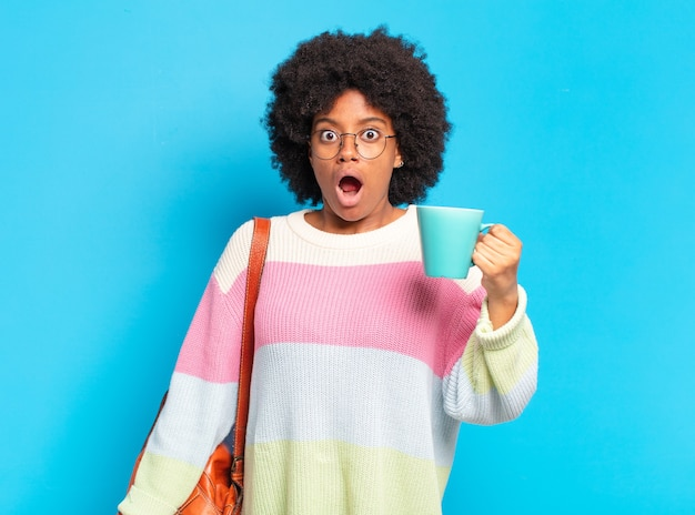 Young pretty afro student woman with a coffee cup