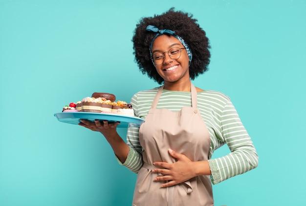 ケーキと若いかなりアフロの女性のパン屋