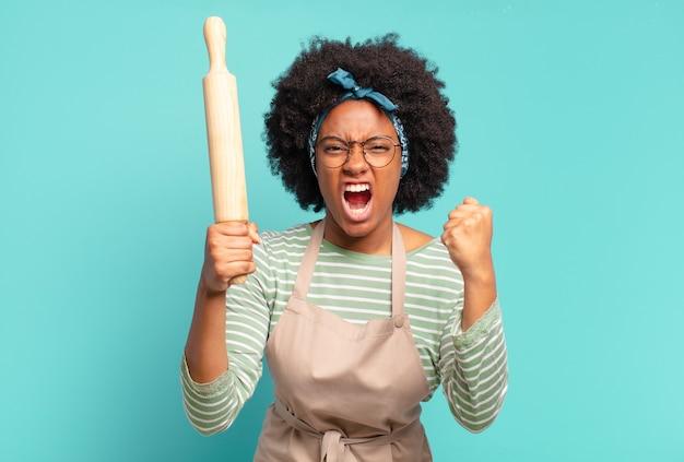 롤링 핀으로 젊은 예쁜 아프리카 여자 요리사