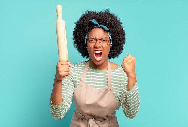Young pretty afro woman chef with a rolling pin
