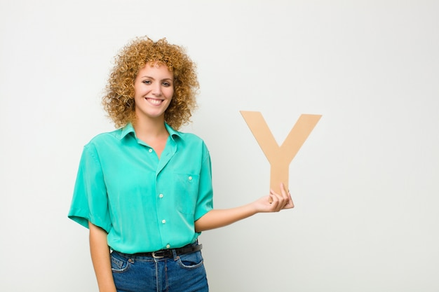 Young pretty afro woman excited, happy, joyful, holding the letter y of the alphabet to form a word or a sentence.