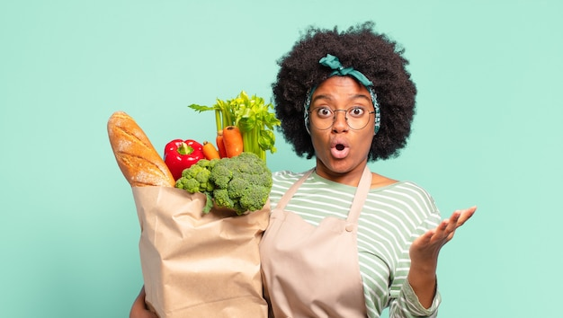 Young pretty afro woman feeling extremely shocked and surprised, anxious and panicking, with a stressed and horrified look and holding a vegetables bag