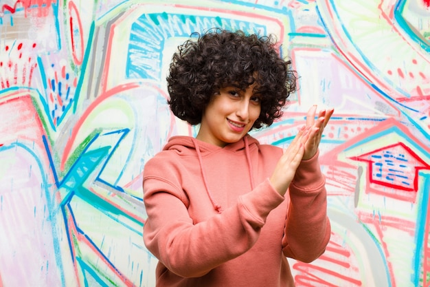 Young pretty afro woman feeling happy and successful, smiling and clapping hands, saying congratulations with an applause against graffiti