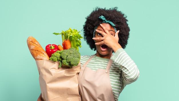 젊고 예쁜 아프리카 여성은 행복하고 놀라고 자랑스러워하며 흥분하고 놀란 표정으로 자신을 가리키며 야채 가방을 들고 있습니다.