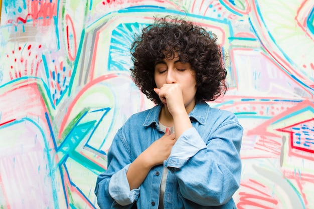 Young pretty afro woman feeling ill with a sore throat and flu symptoms, coughing with mouth covered against graffiti wall