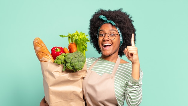 Молодая симпатичная афро-женщина почувствовала себя счастливой и взволнованной гением, реализовав идею, весело подняв палец, эврика! и держит мешок овощей