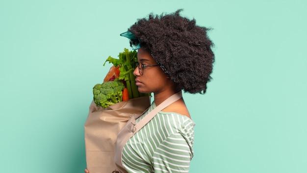 悲しみ、動揺、または怒りを感じ、否定的な態度で横を向いて、意見の相違に眉をひそめ、野菜の袋を持っている若いかなりアフロの女性