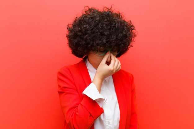 Young pretty afro woman feeling stressed, unhappy and frustrated, touching forehead and suffering migraine of severe headache