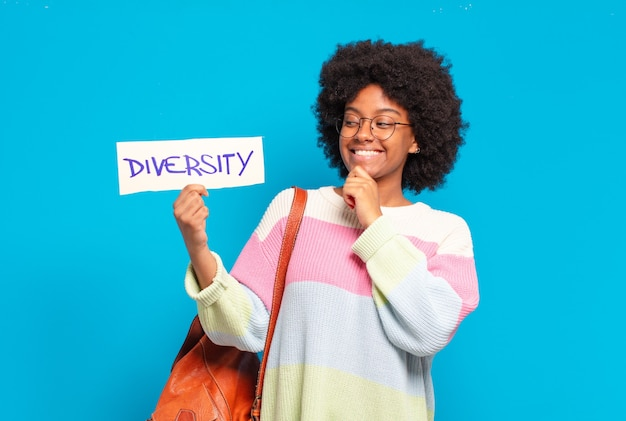 Young pretty afro woman holding diversity banner