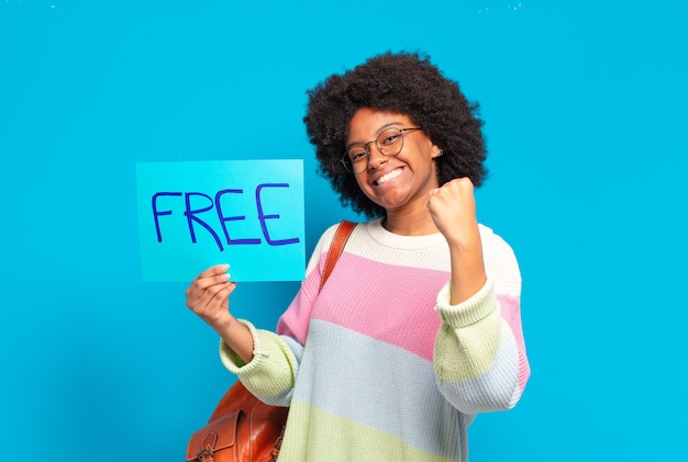 Young pretty afro woman holding free concept banner
