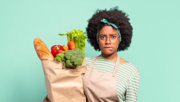 Молодая симпатичная афро-женщина выглядит озадаченной и сбитой с толку, нервно прикусывает губу, не знает ответа на проблему и держит мешок с овощами