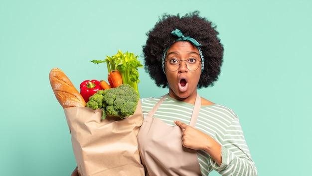 Молодая симпатичная афро-женщина выглядит шокированной и удивленной с широко открытым ртом, указывая на себя и держа мешок с овощами