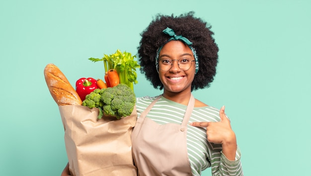 Young pretty afro woman looking very shocked or surprised, staring with open mouth saying wow and holding a vegetables bag