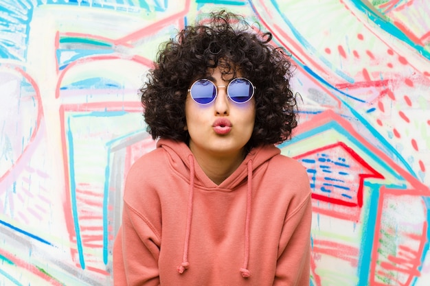 Young pretty afro woman pressing lips together with a cute, fun, happy, lovely expression, sending a kiss against graffiti wall