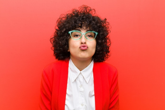 Young pretty afro woman pressing lips together with a cute, fun, happy, lovely expression, sending a kiss
