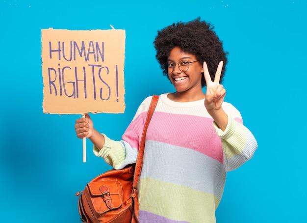 人権バナーで抗議する若いかなりアフロの女性