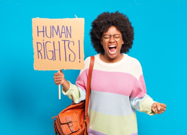 Young pretty afro woman protesting with human rights placard
