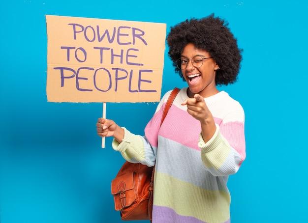 Молодая симпатичная афро-женщина протестует с плакатом: сила народу