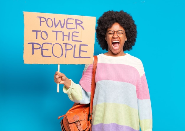 Young pretty afro woman protesting with a power to the people